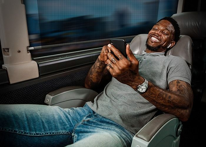 Udonis Haslem checking his phone on a Red Coach USA motorcoach